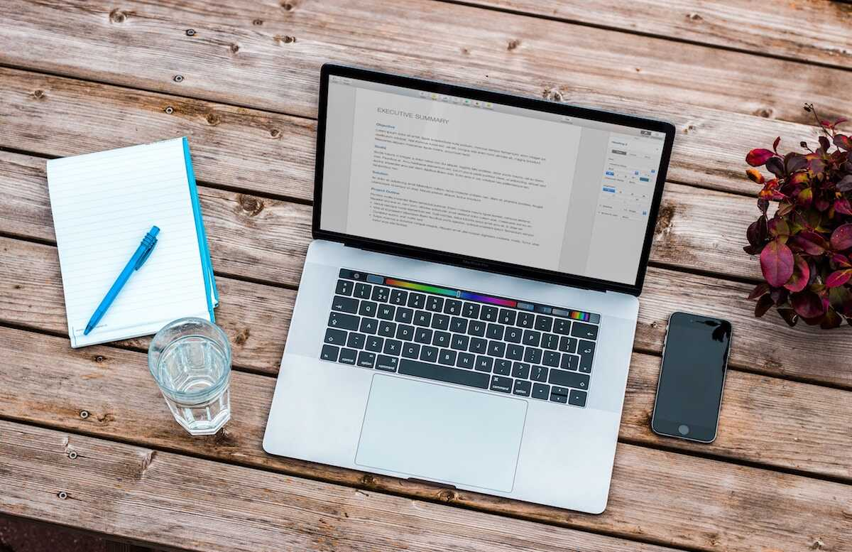 Bench flatlay featuring a MacBook with a CV, notebook and pen, and glass of water
