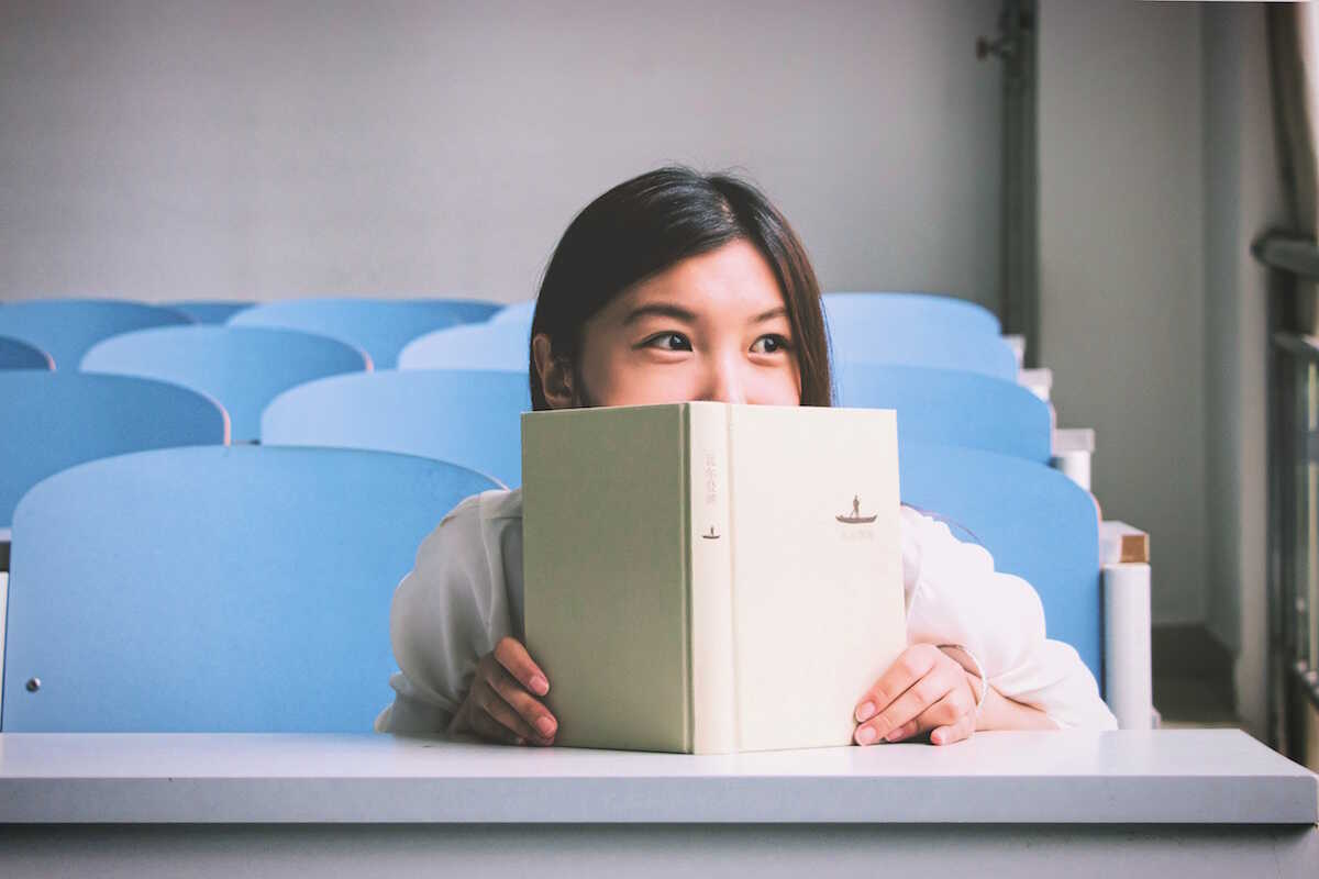 Student in lecture theatre sitting behind a book