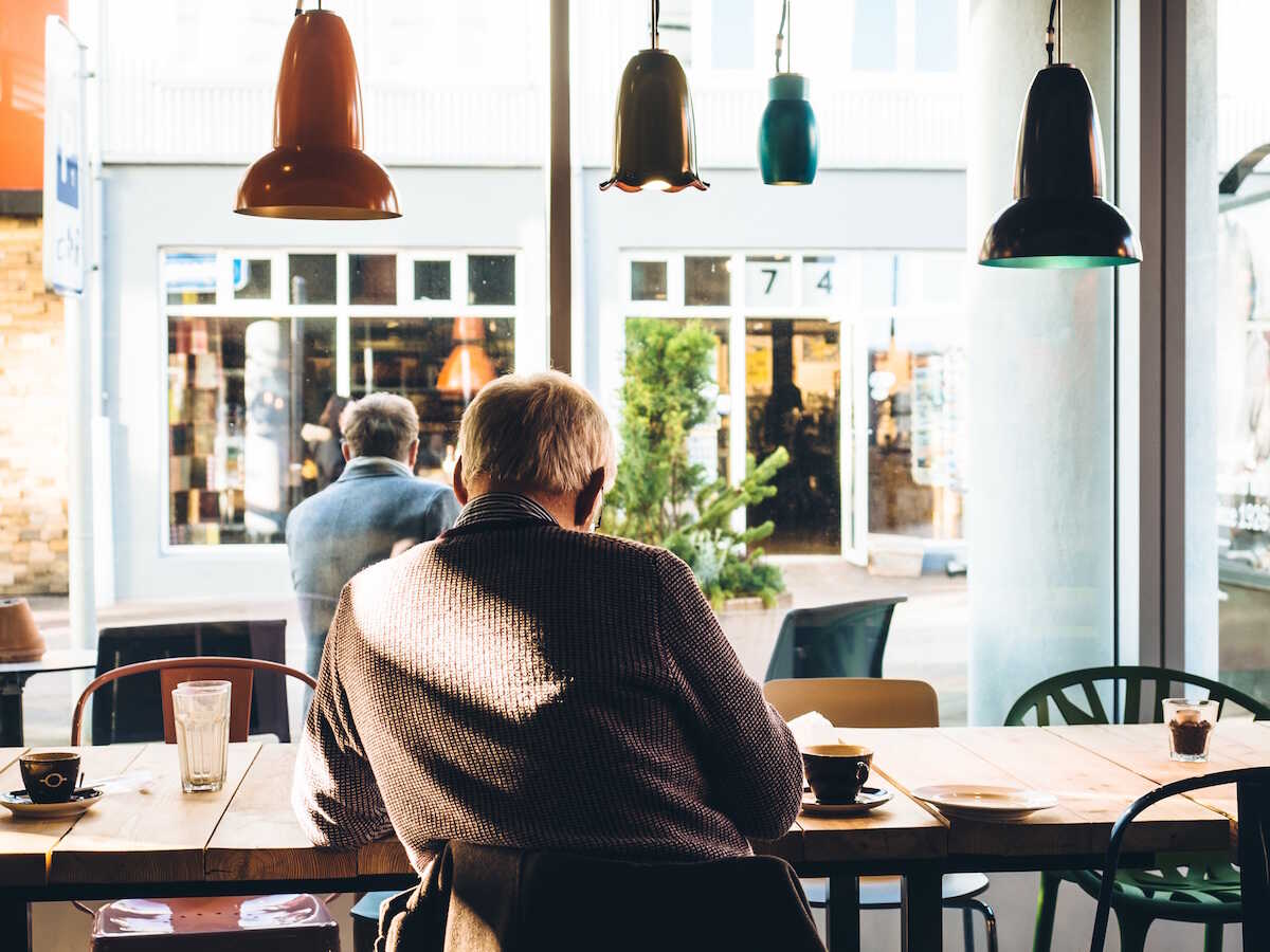An older man sitting in a coffee shop