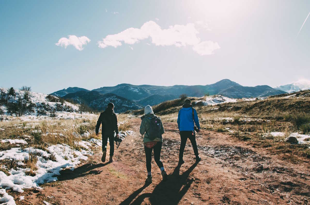 Students walking in the snowy mountains carrying cameras