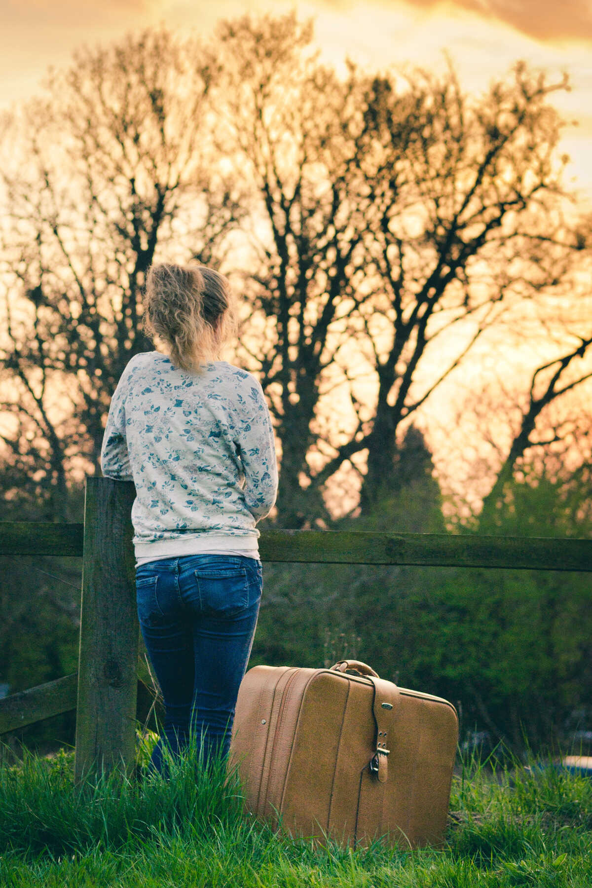 Young female standing away from the camera with a suitcase
