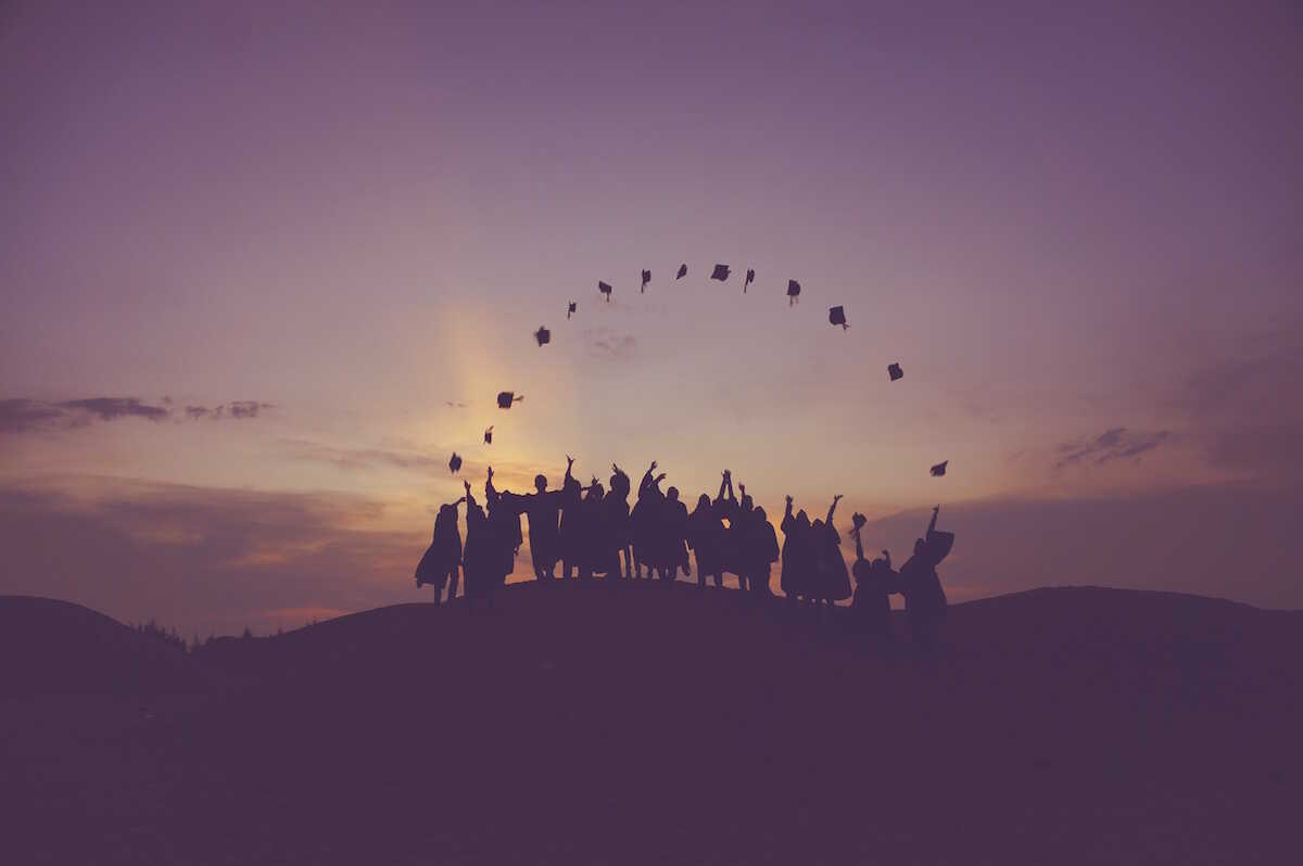 Purple image of graduates on a hill throwing up their mortarboards in a rainbow shape