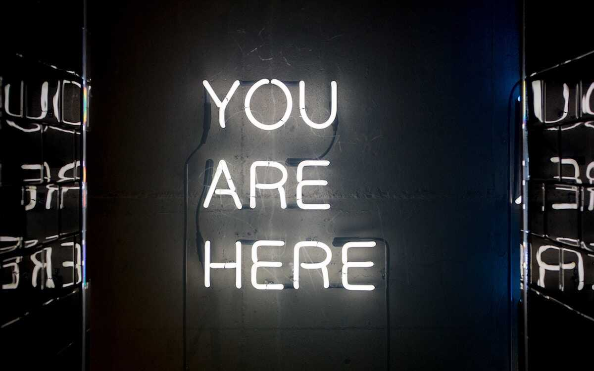 White neon lights saying You Are Here