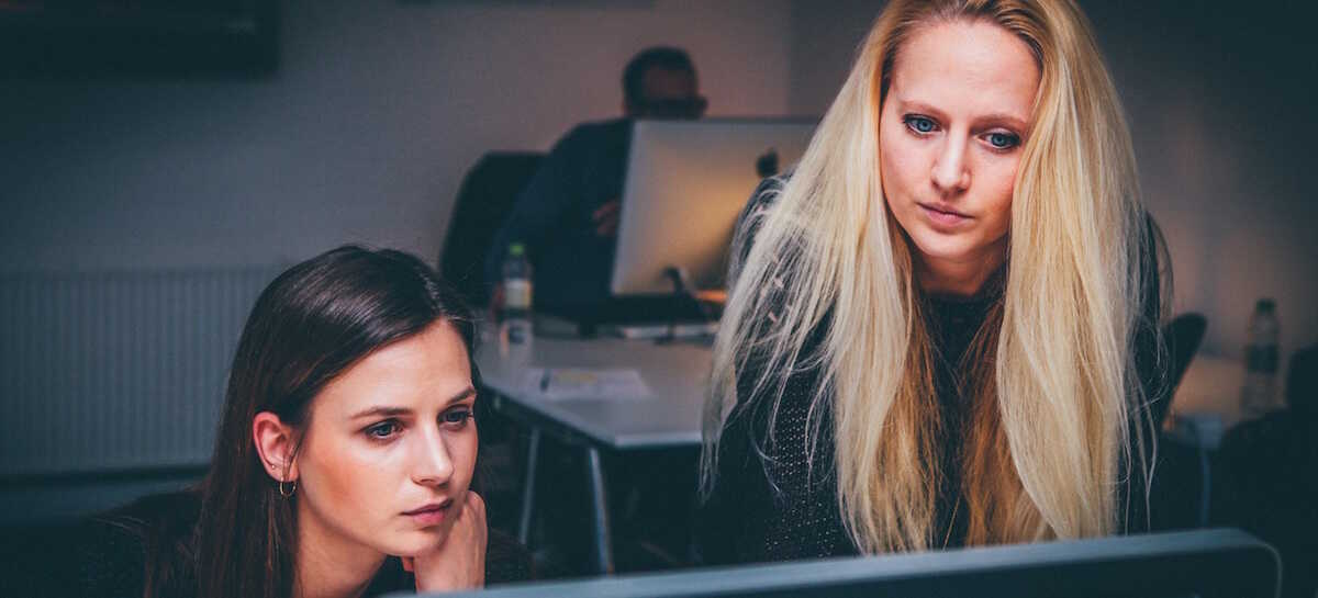 Two women looking at a computer screeen in an office