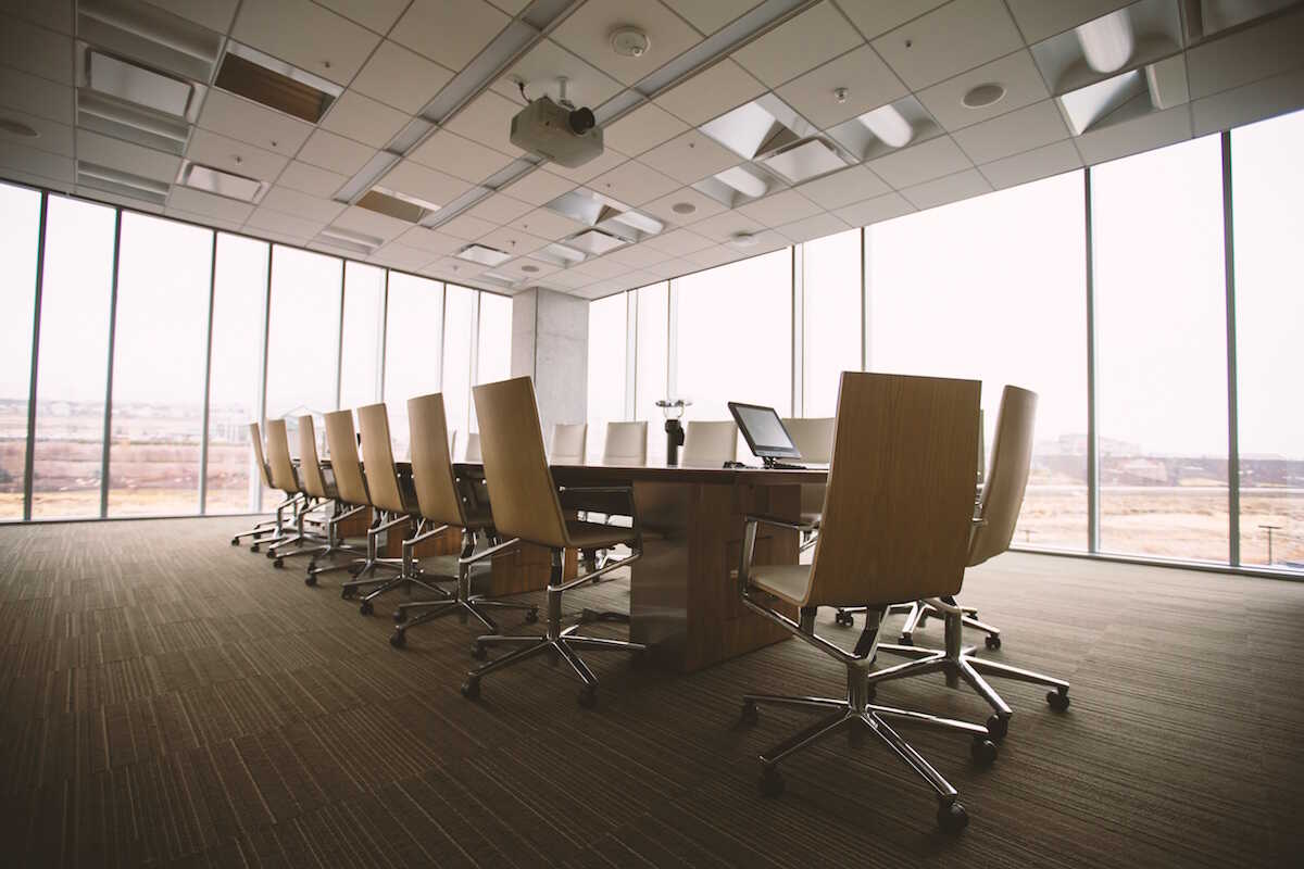 An empty meeting room with a table and chairs surrounded by windows