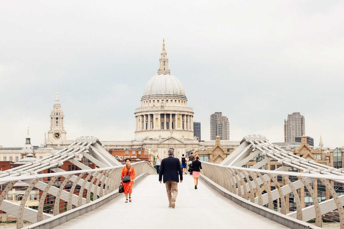 People walking on Millenium Bridge with St Pauls Cathedral in the background