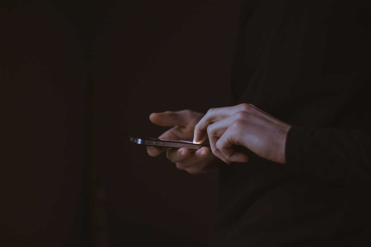 Close up of a man's hands using an iPhone