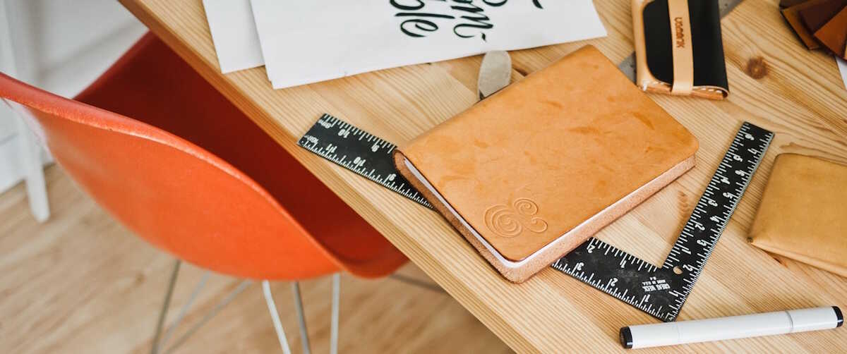 An orange chair next to a table with a notebook, ruler and pen