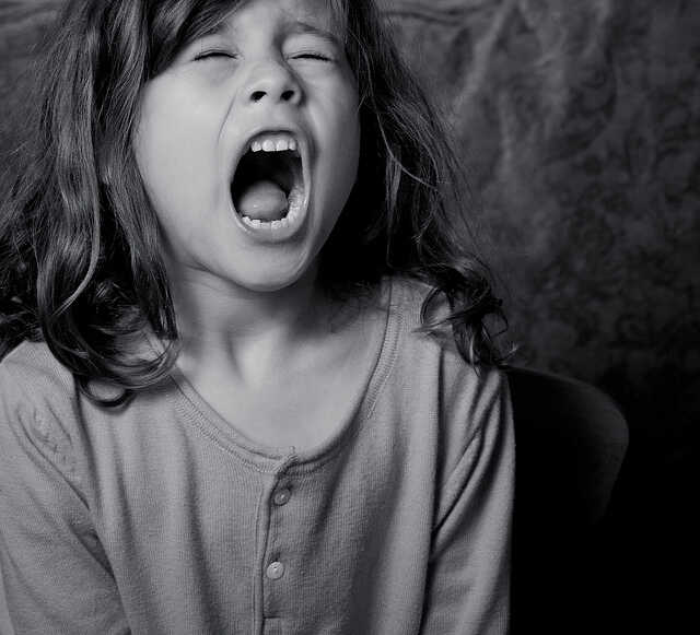 Black and white image of a young girl screaming