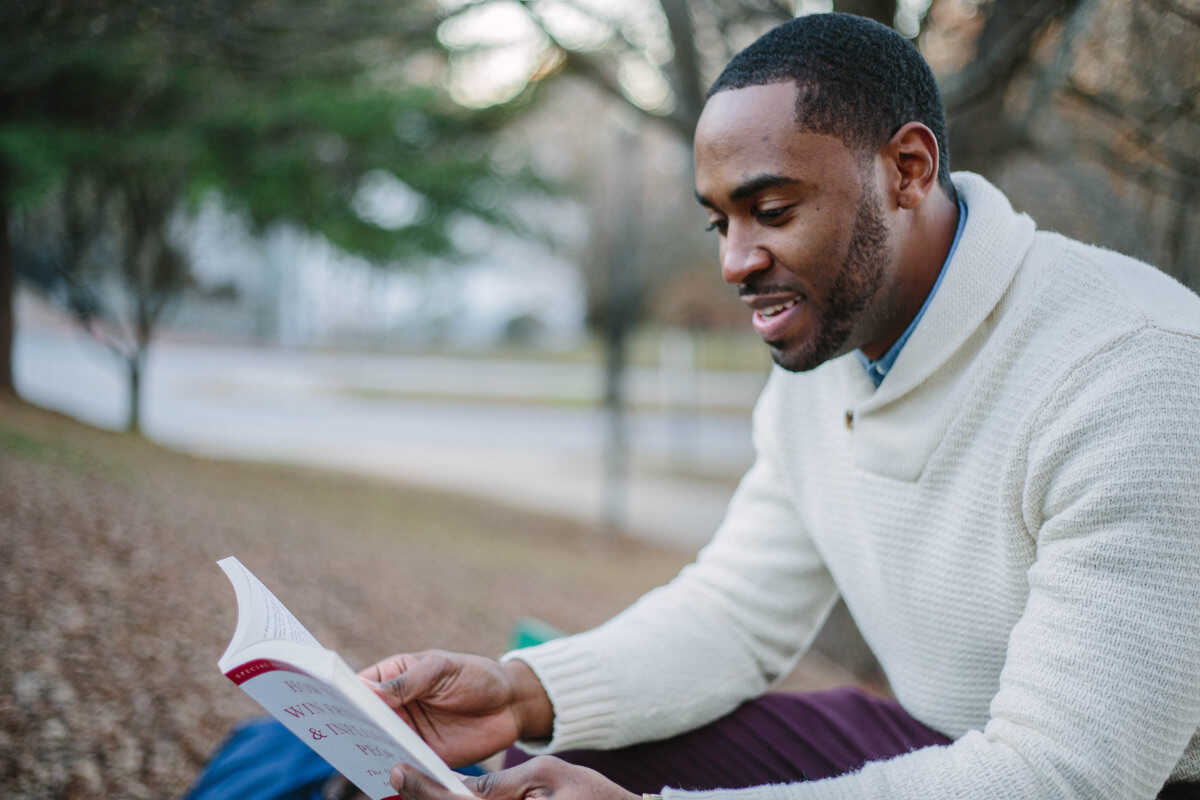 Black man reading a book in the park