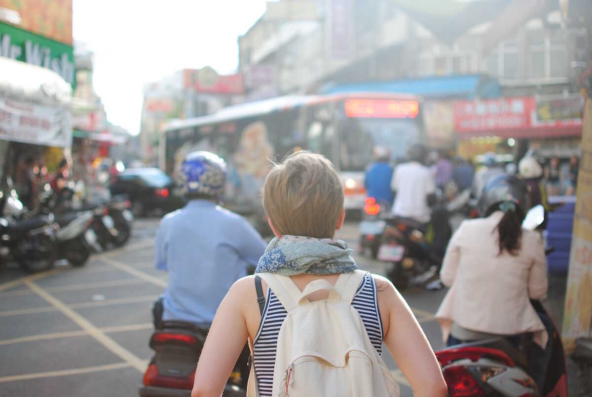 Young woman with a backpack on a busy street