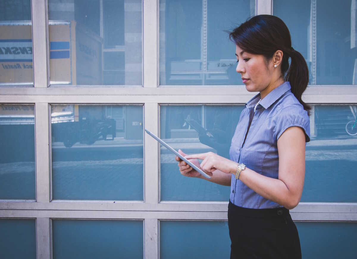 Professional woman walking along looking at a tablet