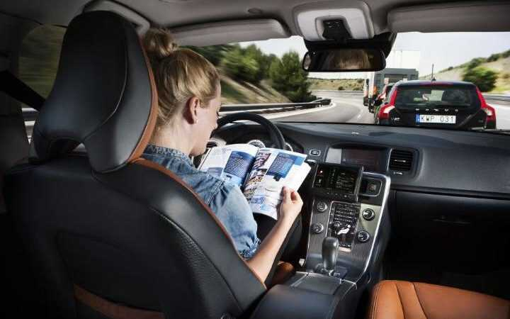 Woman sitting in a driverless car reading a magazine